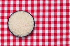 Jarzynowy jedzenie Makro- puchar z uncooked surowymi ryż groszkuje na czerwonym w kratkę tablecloth zdrowe jeść Odgórny widok z p obrazy stock