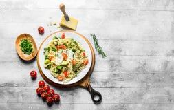 Jarzynowy makaron z sieka? zieleniami w pucharze, pomidorach i Parmeza?skim serze, obraz royalty free