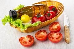 Jarzynowy olej, s?l, li?cie sa?ata, czerwoni pomidory w ?ozinowym koszu, kawa?ki pomidor, n?? na drewnianym stole obraz royalty free