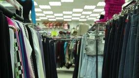 Jasjes en jeans op hangers in opslag stock video