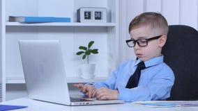 Jaskrawa chłopiec pisać na maszynie na laptopie i ono ono pisze liść zbiory