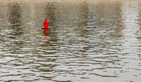 Jaskrawa czerwona metalu boja pławika ocena dla statków na gładkiej wiośnie fotografia royalty free