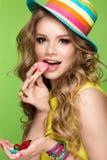 Jaskrawa rozochocona dziewczyna w lato kapeluszu, kolorowy makijaż, kędziory i menchie, robimy manikiur Piękno Twarz Fotografia Royalty Free