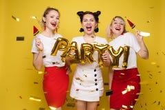 Jaskrawa trzy dziewczyny utrzymuje balony i lody zdjęcia royalty free