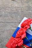 Jaskrawa wakacje karta na Luty 23 Czerwoni goździki i rosjanin zaznaczają na nieociosanym drewnianym tle Fatherland obrońcy dzień fotografia stock