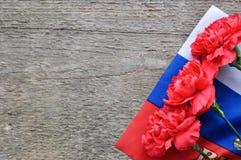 Jaskrawa wakacje karta na Luty 23 Czerwoni goździki i rosjanin zaznaczają na nieociosanym drewnianym tle Fatherland obrońcy dzień zdjęcia royalty free