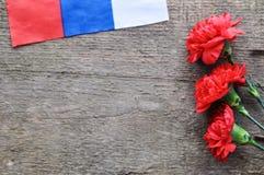 Jaskrawa wakacje karta na Luty 23 Czerwoni goździki i rosjanin zaznaczają na nieociosanym drewnianym tle Fatherland obrońcy dzień obrazy stock