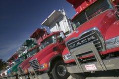 Jaskrawe czerwone Mack usypu ciężarówki wykładają drogę w Maine z rzędu, blisko New Hampshire granicy Zdjęcia Stock