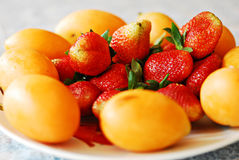 Jaskrawe czerwone truskawki z mangowymi śliwkami Zdjęcia Stock