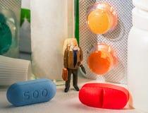 Jaskrawe pigułki i Stara mężczyzna figurka Apteka dla starych ludzi pojęć Zdjęcia Stock