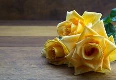 Jaskrawej ampuły otwarte żółte róże zamknięte up na dębowym drewnianym stole - półdupki Obrazy Stock