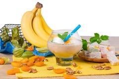 Jaskrawi żółci banany, szkło koktajl z wysuszonymi morelami, orzechy włoscy i liście, wybijają monety, lokum odizolowywający na b Zdjęcia Stock