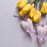 Jaskrawi żółci wiosna tulipany i dwa dekoracyjnego serca na popielatym Obraz Stock