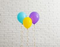 Jaskrawi balony zbli?aj? ?cian? z cegie? fotografia royalty free
