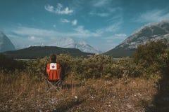 Jaskrawi czerwieni krzesła przegapia trawy i gór z jeziorem w Niskim Kananaskis jeziorze z Canada logem, Kanada zdjęcia stock