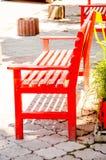 Jaskrawi czerwoni ławka stojaki na chodniczku obraz royalty free