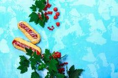 Jaskrawi eclairs z owocowym jagodowym plombowaniem z czerwonym rodzynkiem Na b??kitnym tle, odg?rny widok Przestrze? dla teksta obraz royalty free