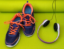 Jaskrawi hełmofony na Staczającej się joga macie i buty Fotografia Stock