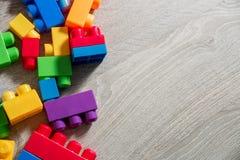 Jaskrawi plastikowi budowa bloki na tle siwieją drewnianego Rozwija zabawki uczenie się wcześniej Rama Odgórny widok Zdjęcie Royalty Free