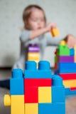 Jaskrawi plastikowi budowa bloki z unrecognizable dziecko dziewczyną na tle Rozwija zabawki uczenie się wcześniej Zdjęcie Royalty Free