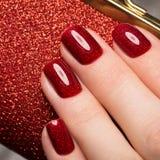 Jaskrawy świąteczny czerwony manicure na żeńskich rękach Gwoździa projekt obraz royalty free