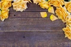 Jaskrawy żółty duży róży granicy tło na starych drewnianych podłogowych śliwkach Obrazy Stock