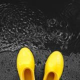 Jaskrawy żółty gumowych butów stojak w deszczu na czarnym tle zakrywającym z kroplami, blisko kałuży zdjęcia royalty free