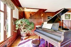 Jaskrawy żywy pokój z drewnianymi panelu podstrzyżenia ścianami i uroczystym pianinem Zdjęcia Royalty Free