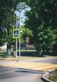 Jaskrawy błękitny i żółty zwyczajny crosswalk znak na grodzkiej ulicie z ruchu drogowego ostrzeżeniem Zdjęcia Stock