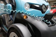 Jaskrawy błękitny i czarny samochód Renault Twizy podładowywa na Stut obraz stock