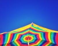 Jaskrawy coloured pasiasty plażowy parasol i jasny niebieskie niebo zdjęcie stock