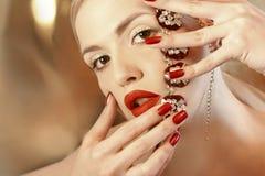 Jaskrawy czerwony manicure na gwoździach i czerwonej pomadce Zdjęcie Stock