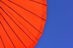 Jaskrawy czerwony parasol przeciw niebieskiemu niebu fotografia royalty free