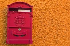 Jaskrawy czerwony poczta pudełko z dwa białymi kopertami na jaskrawej żółtej pomarańcze ścianie loket czeska republika obraz stock