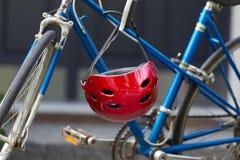 Jaskrawy czerwony rowerowy hełma obwieszenie od rękojeść barów Fotografia Stock