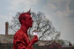 Jaskrawy czerwony występu artysta trzyma kryształową kulę z nagimi drzewami w tle Obrazy Stock