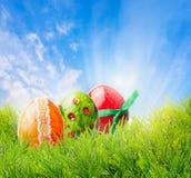Jaskrawy Easter jajko na trawie nad niebieskim niebem z sunrays Fotografia Royalty Free