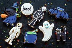 Jaskrawy Halloween ciastek piernikowy tło z nietoperzem, czarownica, kościec, duch na czarnego tła odgórnym widoku Fotografia Stock