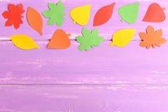 Jaskrawy jesieni tło dla dzieciaków, dzieciniec Jesień papier opuszcza na błękitnym drewnianym tle z pustą przestrzenią dla tekst Zdjęcia Stock