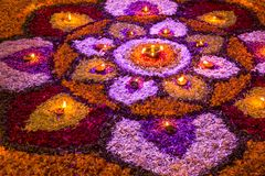 Jaskrawy kolorowy mandala świezi kwiaty z płonącymi świeczkami przy noc festiwalem Diwali zdjęcie stock
