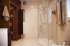 Jaskrawy nowy łazienki wnętrze z szklanym spacerem w prysznic obwódce, brąz bezcelowości gabinet i dobierać do pary z mozaiki pły zdjęcie royalty free
