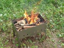 Jaskrawy płomień wybuchał łupkę w małym przenośnym węgla drzewnego grillu Fotografia Stock