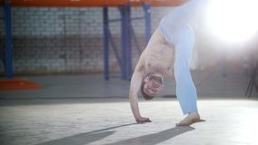 Jaskrawy pok?j Sportowy bez koszuli mężczyzna trenuje jego capoeira doskakiwanie na jego i umiejętności ręki zdjęcie wideo