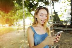 Jaskrawy portret z światłem słonecznym młody blondynki dziewczyny gawędzenie smartphone i jazda huśtamy się w Bali, piasek w tle zdjęcie royalty free