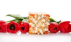 Jaskrawy prezenta pudełko z łękiem i tulipanami fotografia stock