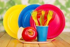 Jaskrawy, rozporządzalny tableware na abstrakt zieleni, Zdjęcia Royalty Free