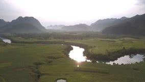 Jaskrawy słońce chujący chmurami odbija w spokojnej wijącej rzece zbiory