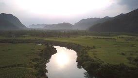 Jaskrawy słońce odbija w spokojnej rzece przeciw arachidowym polom zbiory