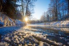 Jaskrawy słońce wzrasta nad zamarzniętą rzeką w zimie krajobrazu wiejskiego obrazy stock