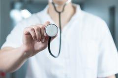 Jaskrawy zakończenie w górę samiec lekarki w mundurze z stetoskopem Słuchający stetoskop i trzymający kosmos kopii obraz royalty free